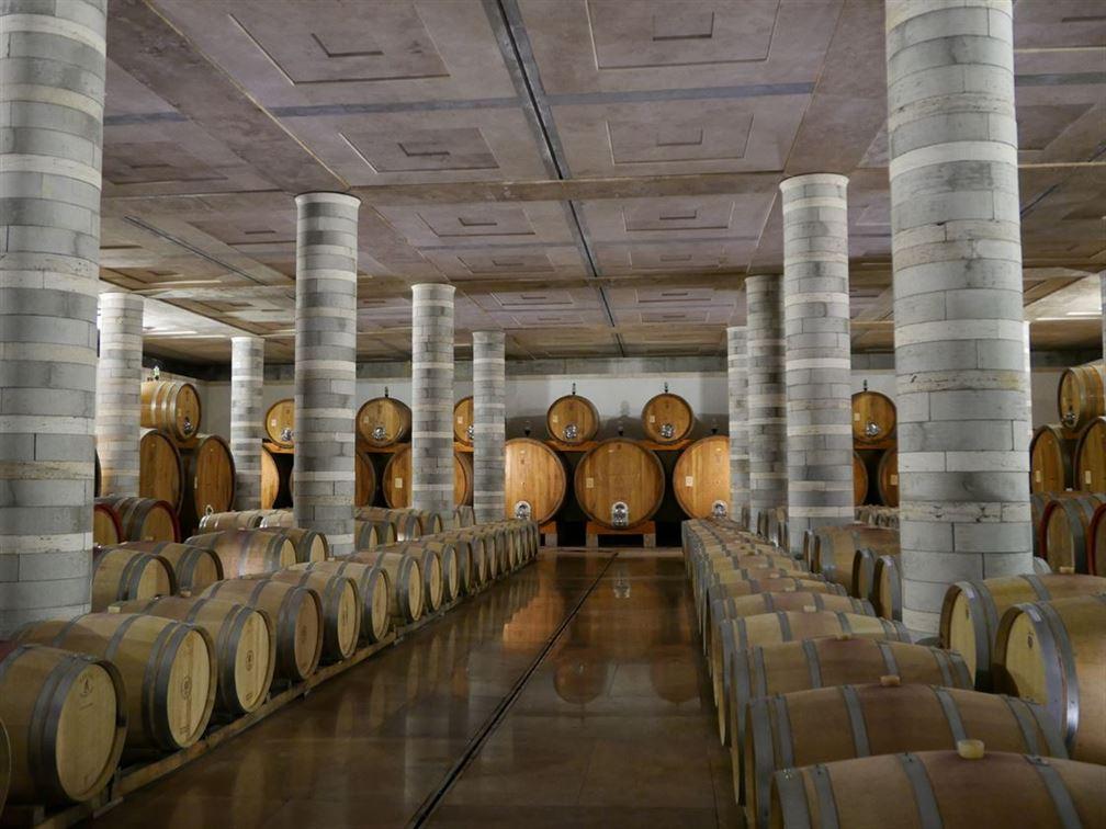 Spectaculaire chai souterrain à barriques construit en pierre calcaire de Toscane